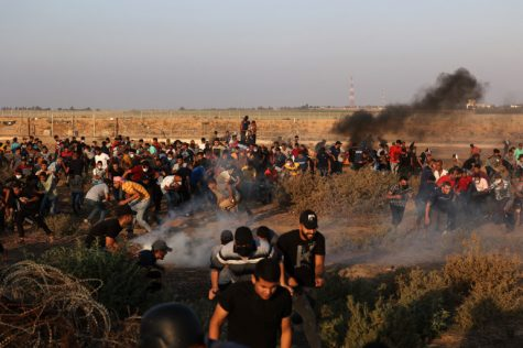 Palestinian demonstrators run from tear gas fired by Israeli security forces during a protest along the border fence, east of Khan Yunis in the southern Gaza Strip, on August 25, 2021. (Photo by MAHMUD HAMS / AFP)